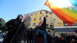 "Genevieve Legay, an Attac activtist, waves a coloured flag during a rally by the anti-government ""Yellow Vests"" (Gilets jaunes) movement in the city of Nice, southeastern France, on March 23, 2019. Thousands of police fanned out across central Paris, Toulo"