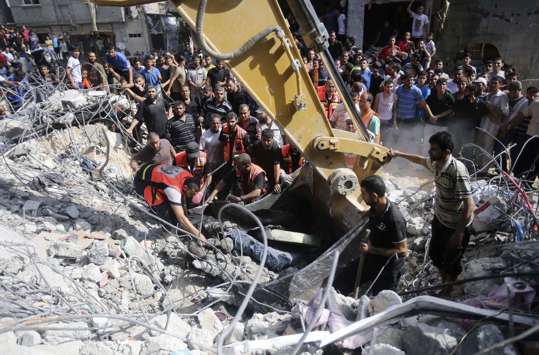Falasdinawa na aikin tono gawawwaki a benen da hare haren Isra'ila suka tarwatsa a Gaza.