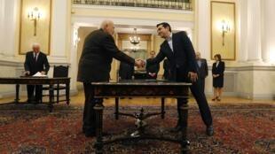 O novo primeiro-ministro grego, Alexis Tsipras (esquerda) cumprimenta o presidente Carolos Papoulias, durante a cerimônia de posse, em Atenas, nesta segunda-feira (26).