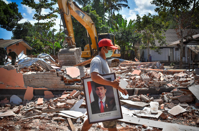 Alors que les pelleteuses fouillent les décombres, le portrait du président Joko Widodo a été sorti des ruines d'une école à Lombok, le 12 août 2018.