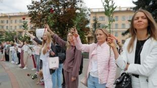 Des femmes tiennent des fleurs lors d'un rassemblement contre la violence suite aux récentes manifestations pour rejeter les résultats de l'élection présidentielle à Minsk, en Biélorussie, le 20 août 2020.