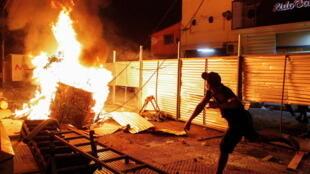 Um manifestante perto de uma barricada em chamas durante a noite de violentos protestos em Assunção, capital do Paraguai. Em 6 de março de 2021.