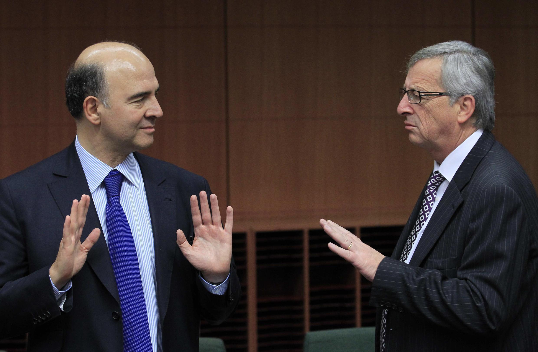 O ministro das Finanças francês, Pierre Moscovici (à esq.) e o presidente do Eurogrupo, Jean-Claude Juncker, durante reunião de ministros das Finanças da zona do euro em Bruxelas.