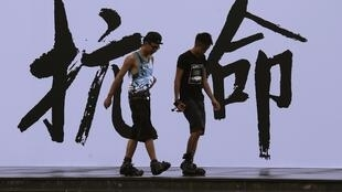 """Pro-democracy activists walk past a backdrop with Chinese characters that read """"disobedience"""", built for an Occupy Central civil disobedience campaign, near the financial Central district in Hong Kong August 31, 2014."""