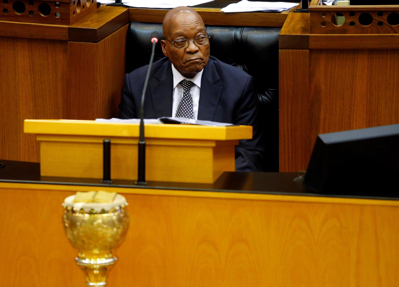O presidente Jacob Zuma ficou impassível no Parlamento enquanto deputados da oposição o acusaram de desvio de dinheiro público.