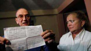 Le dissident cubain Hector Maseda (G) présente debout à côté de sa femme Laura Pollan (D) dirigeante de l'organisation les Dames en blanc, l'avis de mise en liberté dans sa résidence de la Havane, le 12 février 2011.