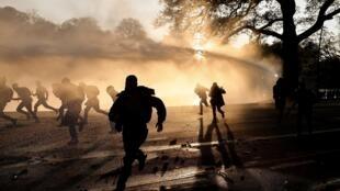 Varias personas huyen de los cañones de agua de la policía antidisturbios que dispersó a los concentrados en una fiesta prohibida en el parque del Bois de La Cambre, el 1 de mayo de 2021 en Bruselas