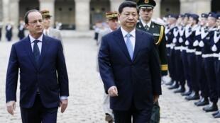 François Hollande (e) caminha ao lado de Xi Jinping no Hotel Nacional dos Invalides