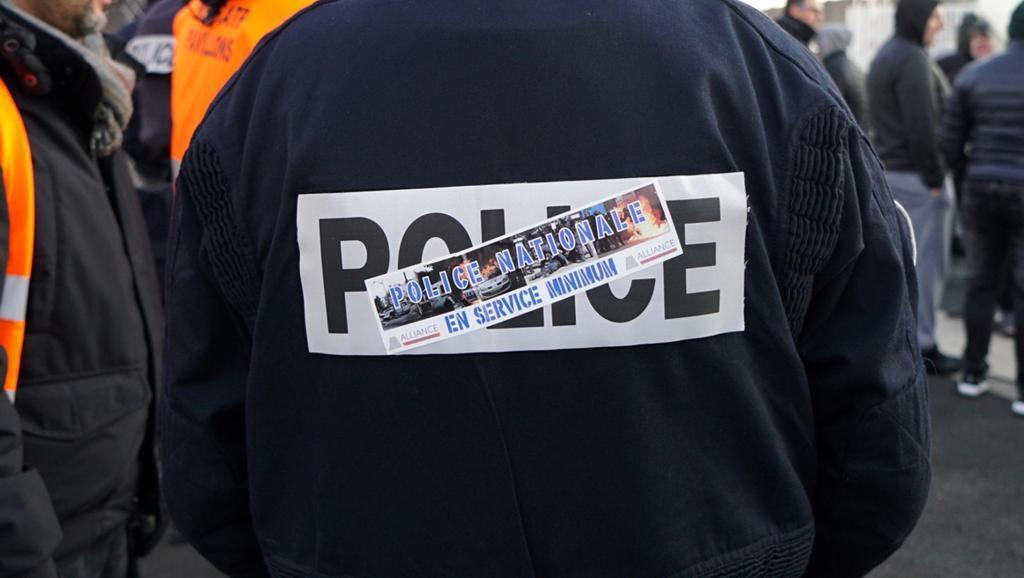 """Um policial francês com um adesivo """"Polícia francesa, serviço limitado"""" se posiciona como sindicalista francês e funcionários da Rede de Transporte de Paris (RATP) bloqueando um depósito de ônibus da RATP em Les-Pavillons-sous-Bois, perto de Paris."""