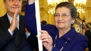 Simone Veil, accompagnée de Jacques Chirac, présente son épée d'académicienne reçue lors d'une cérémonie au Sénat, le 16 mars 2010, et sur laquelle elle a fait graver la devise de la France : Liberté, Egalité, Fraternité.