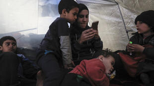 A mother detained with her children at a camp for Islamic State (IS) group-affiliated people in the northern Syrian village of Ain Issa, gestures during an interview on February 15, 2018.