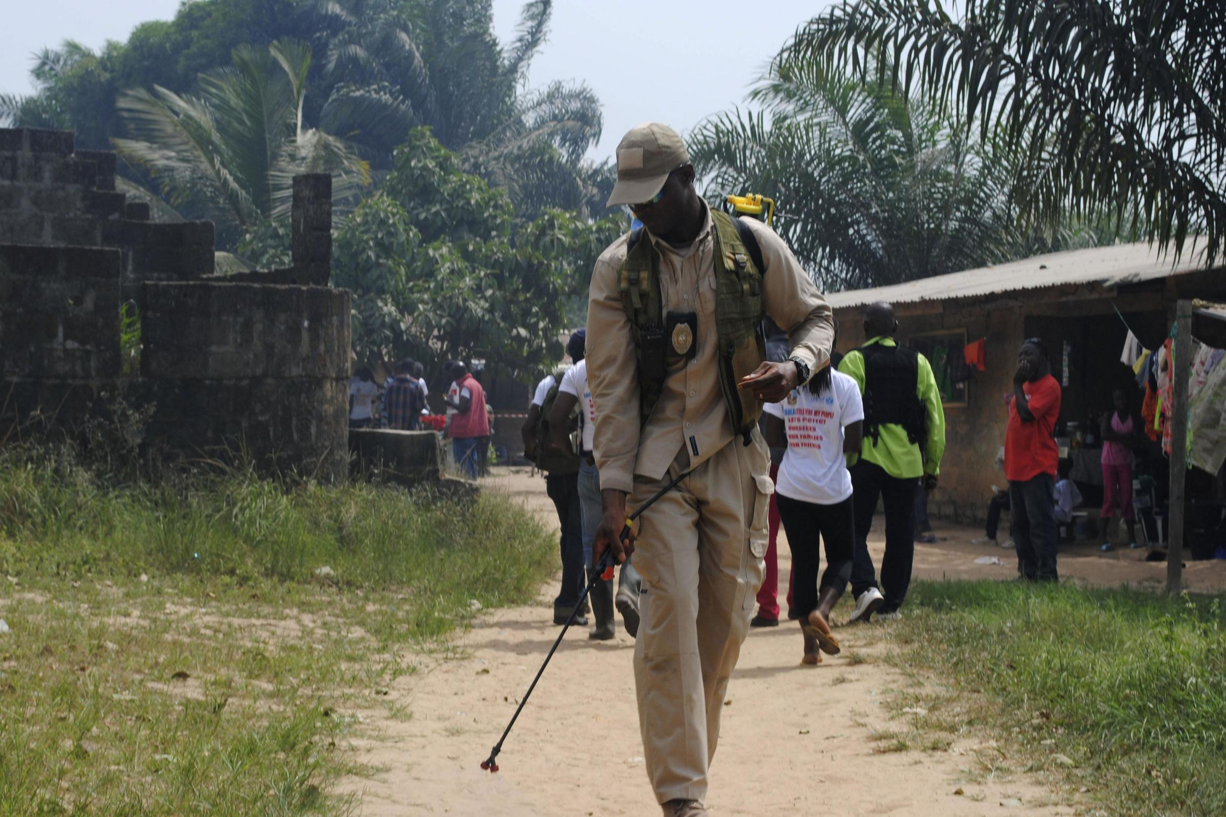 A health worker disinfects a road in the Paynesville neighborhood of Monrovia in Liberia