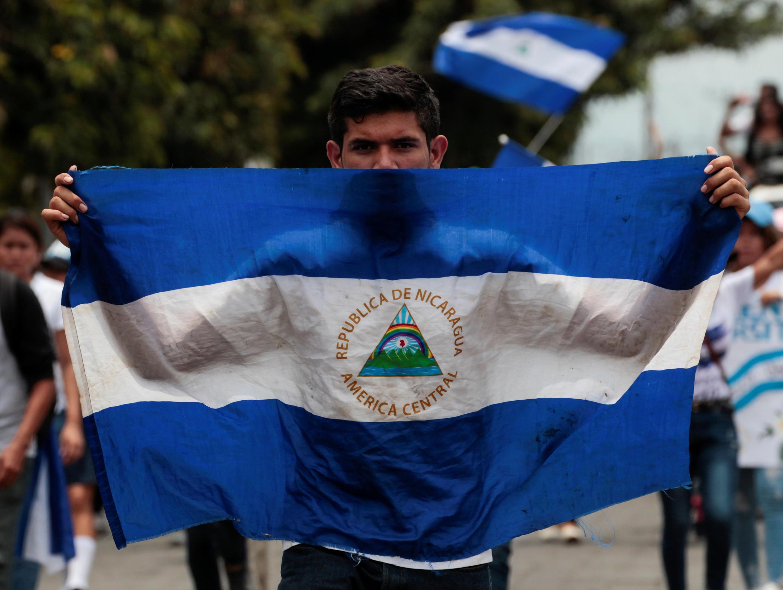 Un manifestant brandit un drapeau du Nicaragua, le 14 mai 2018 dans une rue de Managua.
