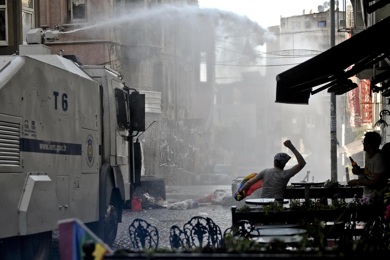 Un drapeau arc-en-ciel dans une main, une pierre dans l'autre, ce participant de la dernière Gay Pride d'Istanbul, le 28 juin 2015, se montre peu impressionné par les canons à eau de la police anti-émeute.