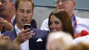 Hoàng tử Anh William sử dụng iPhone để xem các trận thi đấu Olympic môn bơi lội, cùng với vợ là Catherine. Ảnh chụp ngày 03/08/2012.