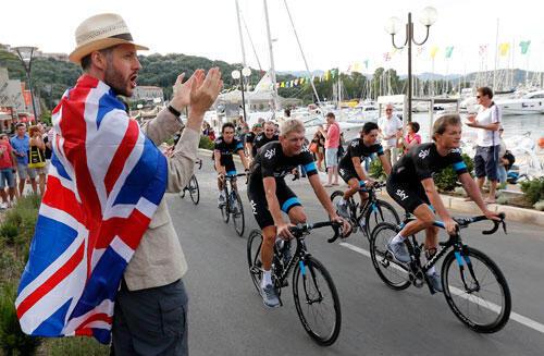 Un fanatique salue les coureurs de l'équipe Sky riders passant par le port, lors de la cérémonie d'ouverture du centenaire du Tour de France à  Porto Vecchio, le 27 juin 2013.