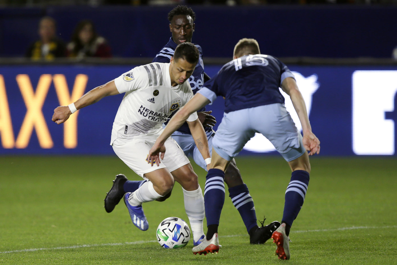 Janio Bikel, médio luso-guineense do Vancouver Whitecaps, numa jogada em que se encontra atrás do avançado mexicano Javier Hernández, conhecido por ter jogado no Manchester United, ele que representa o Los Angeles Galaxy.