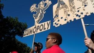 Une manifestante brandit une caricature de l'un des frères Gupta lors d'une mobilisation contre les affaires entourant Jacob Zuma, le 7 août 2017.