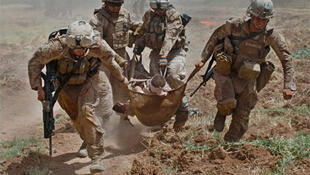 US Marines carry a wounded colleague in Helmand Province, Afghanistan. The number of US casualties is far higher than French.