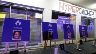 Des portraits de victimes sont posés à l'extérieur du supermarché Hyper Cacher, dans le sud de Paris, le 9 janvier 2020, lors d'une cérémonie commémorative après la prise d'otages meurtrière.