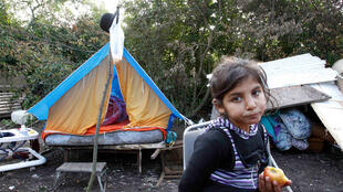 A young girl from a Roma family eats an apple near a make-shift tent shelter in Lesquin, northern France