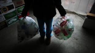 Une femme détient des sacs de bouteilles vides à trier à Sure We Can, un centre de rachat de bouteilles à but non lucratif à Bushwick, Brooklyn.