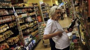 Consumidora compara preços em supermercado de São Paulo