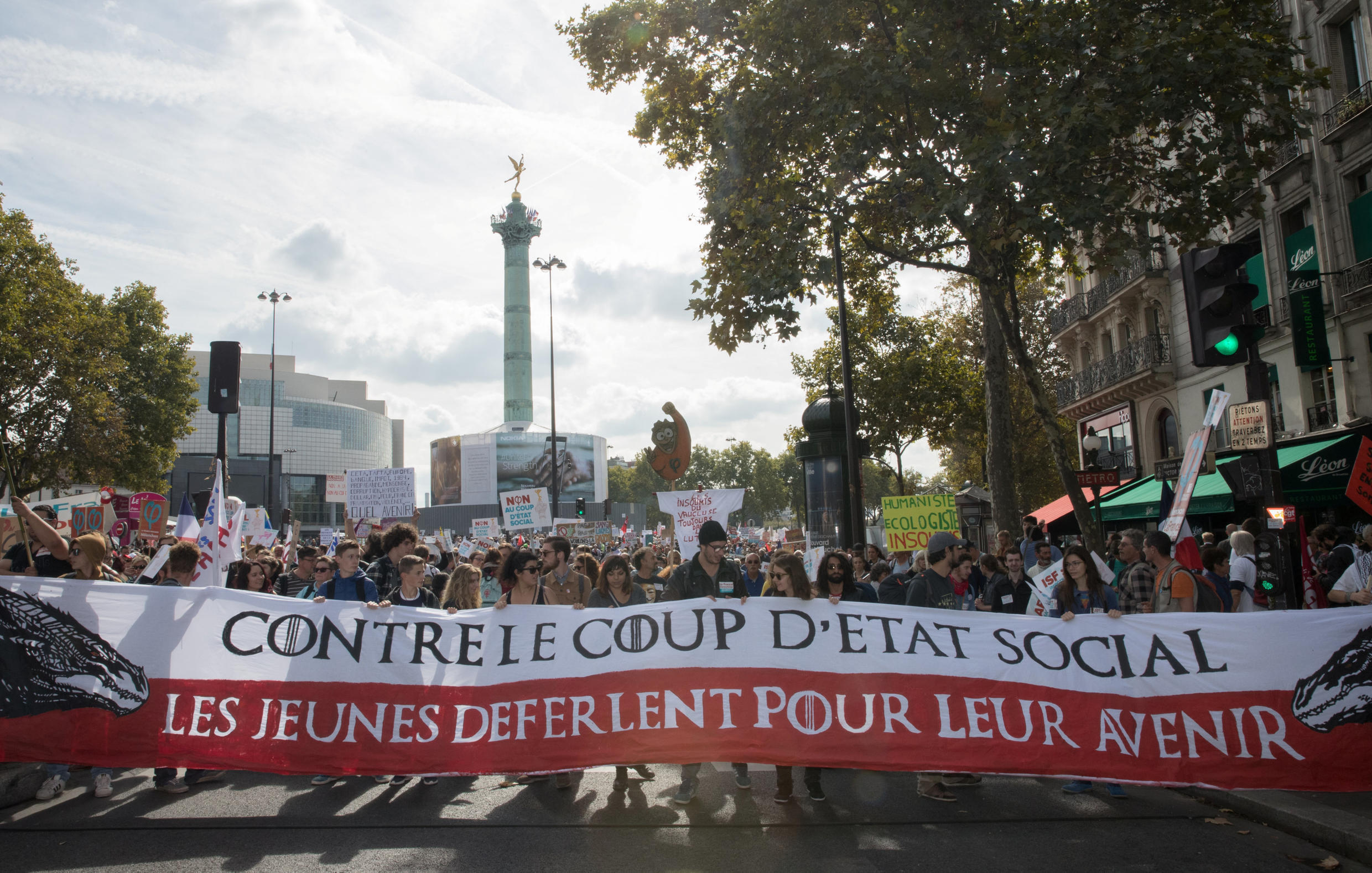 """Protestors march behind a banner reading """"against the social coup, youth flood on the streets for their future"""" during a """"France Insoumise"""" (France Unbowed) party's demonstration against the government's labour reforms in Paris, France, September 23, 2017."""