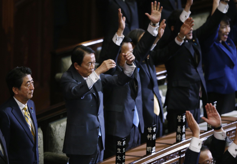 Le Premier ministre Shinzo Abe (g.) est resté impassible après l'annonce officielle de la dissolution du Parlement japonais, le 21/11/14.