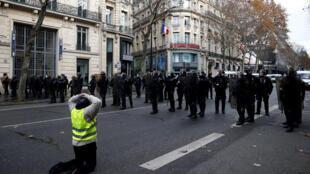 Un «gilet jaune» face aux forces de l'ordre en position, le 8 décembre 2018 à Paris.