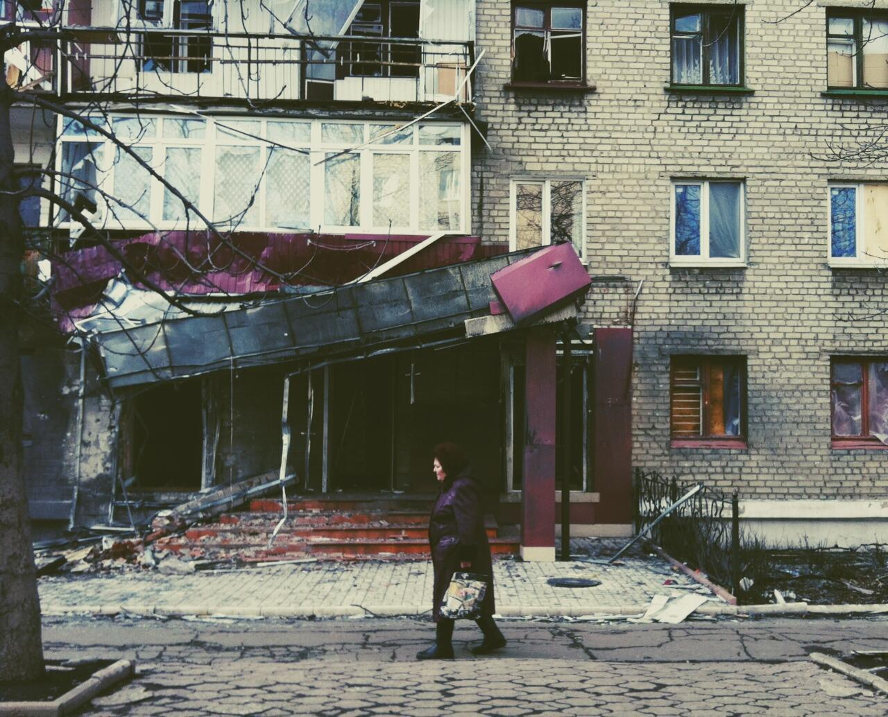 Женщина идет мимо разрушенного дома в Дебальцево, 6 марта 2015 года