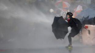 一名反政府示威者打開雨傘竭力抵擋警方水炮車襲擊