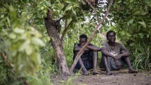 Deux déplacés en raison des violences au Katanga devant une cabane précaire.