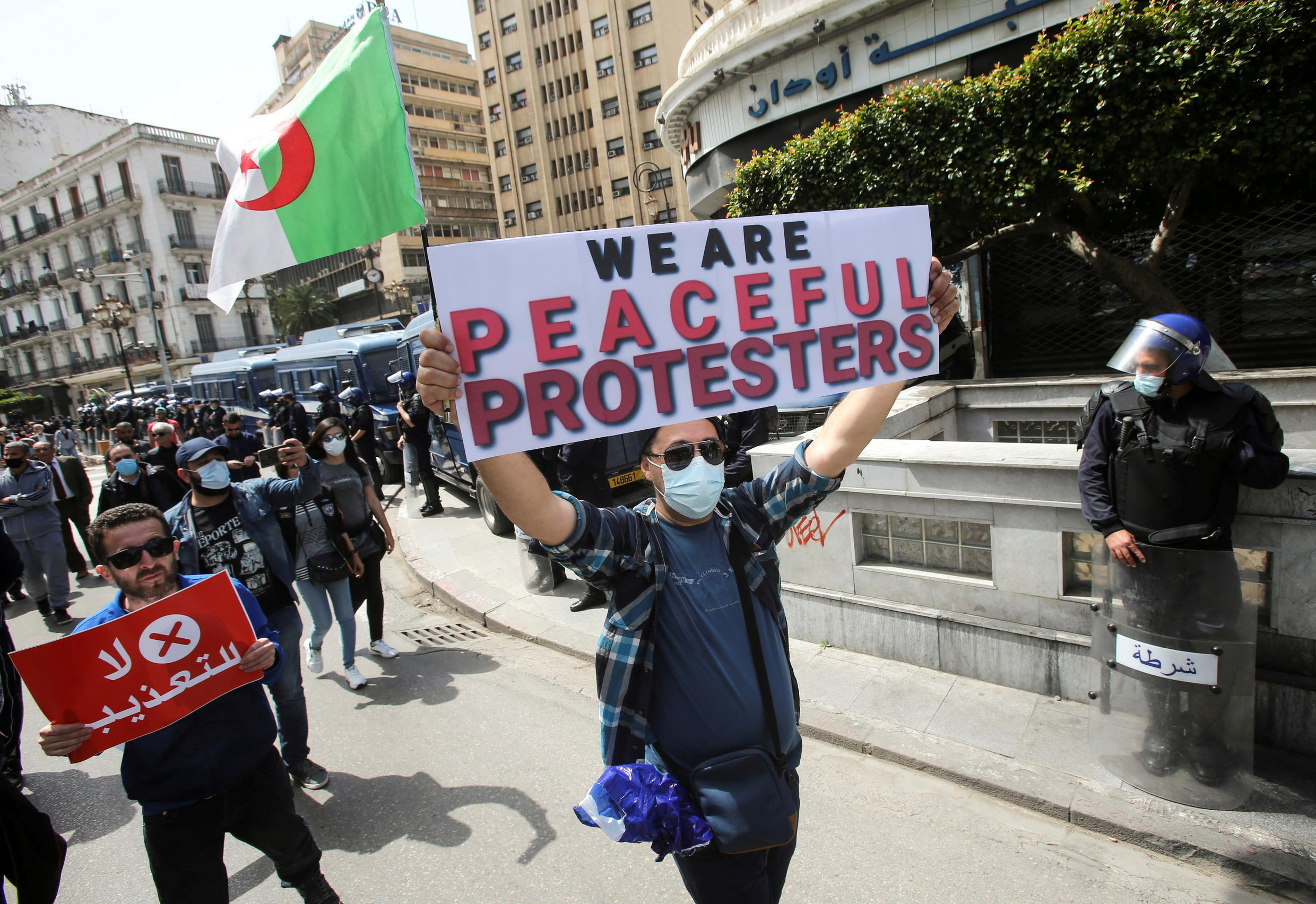 FILE PHOTO: Demonstrators march with banners and flags during a protest demanding political change, in Algiers, Algeria April 9, 2021.