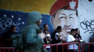 Венесуэльские избиратели на фоне портрета Уго Чависа, 30 июня 2017 г.