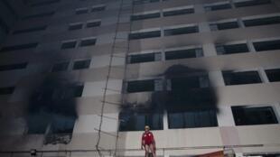 Пожарный возле источника возгорания на швейной фабрике в Дакке 09/05/2013