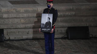 A French Republican Guard holds a portrait of Samuel Paty in Paris on 21 October 2020, during a national homage to the teacher, who was beheaded for showing cartoons of the Prophet Mohamed during a civics class.