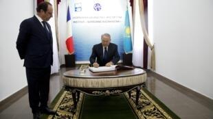 Le président François Hollande (G.) et son homologue kazakh, Noursoultan Nazarbaïev (D.), signent le livre d'or, lors de linauguration de l'institut Sorbonne-Kazakhstan, à Almaty, le 6 décembre 2014.