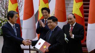 Thủ tướng Nhật Shinzo Abe (T) và thủ tướng Việt Nam Nguyễn Xuân Phúc (P) vỗ tay sau buổi ký kết thỏa thuận. Ảnh ngày 16/01/2017 tại Hà Nội.