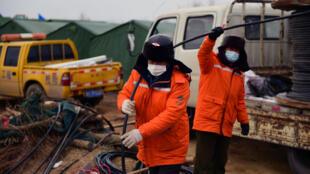 Dos miembros de un equipo de rescate desplegado en una mina de oro de Qixia, en el este de China, donde 22 trabajadores quedaron atrapados tras una explosión