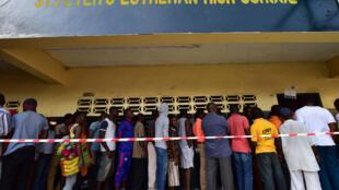 Des Libériens font la queue aux abords d'un bureau de vote le 10 octobre 2017 à Monrovia, la capitale.