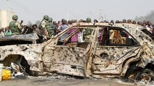 Multidão de nigerianos observa carro que explodiu durante ataque terrorista do grupo Boko Haram, nos arredores de Abuja.