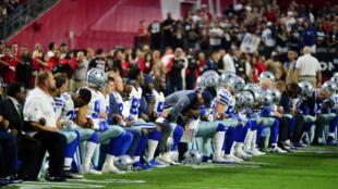 Les Dallas Cowboys, équipe de football américain, agenouillés avec leur staff et leurs entraineurs pendant l'hymme national, le 25 septembre 2017 à Phoenix.