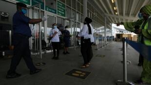 Des agents de l'aéroport d'Abuja au Nigeria indiquent aux passagers la marche à suivre pour respecter les mesures sanitaires prises en réponse à la pandémie de Covid-19, le 8 juillet 2019