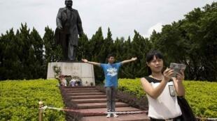 Khách du lịch chụp hình kỷ niệm trước tượng Đặng Tiểu Bình tại Thâm Quyến, Quảng Đông. Ảnh chụp ngày 19/08/2014.