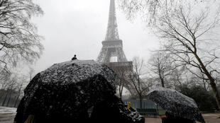 People use umbrellas to take cover from falling snow near the Eiffel Tower in Paris, as winter weather with snow and freezing temperatures arrive in France, February 5, 2018.