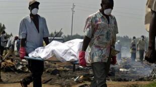 Des volontaires tranportent les corps des victimes du massacre à Gatumba. Le 14 aout 2004.