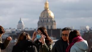 Mulher usa máscara protetora em frente à Esplanada dos Inválidos