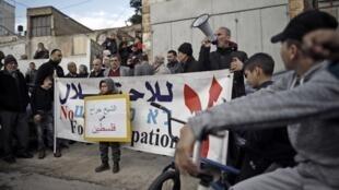 Des militants pour la paix scandent des slogans près de la maison de la famille Sabbagh menacée d'expulsion imminente, dans le quartier de Sheikh Jarrah de Jérusalem-Est, le 18 janvier 2019.