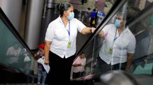 Une femme porte un masque de protection, après les premiers cas de coronavirus dans le pays, à l'aéroport international de Toncontin à Tegucigalpa, au Honduras, le 12 mars 2020.